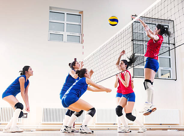 teenage girl team playing volleyball. - volleyball stock photos and pictures