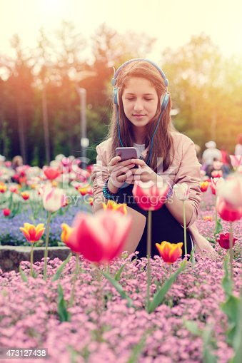623358818 istock photo Teenage girl texting on smartphone in the park 473127438