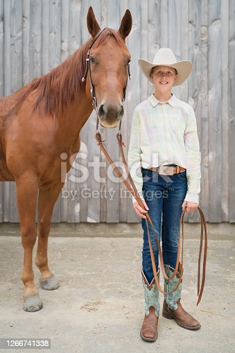 Blonde teenage girl dressed in Western Riding - Horseback Riding Outfit standing side by side next to her beautiful brown horse in front of wooden stable. Smiling bright and happy to the camera. Real People Horseback Riding Portrait