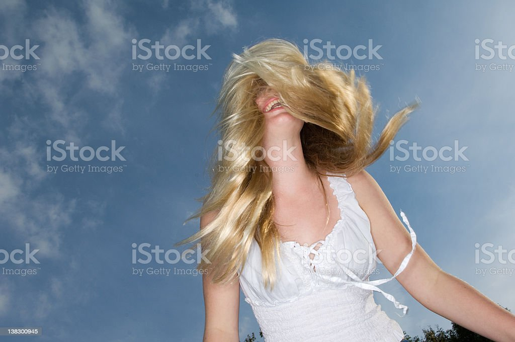 Teenage girl tossing her hair outdoors stock photo