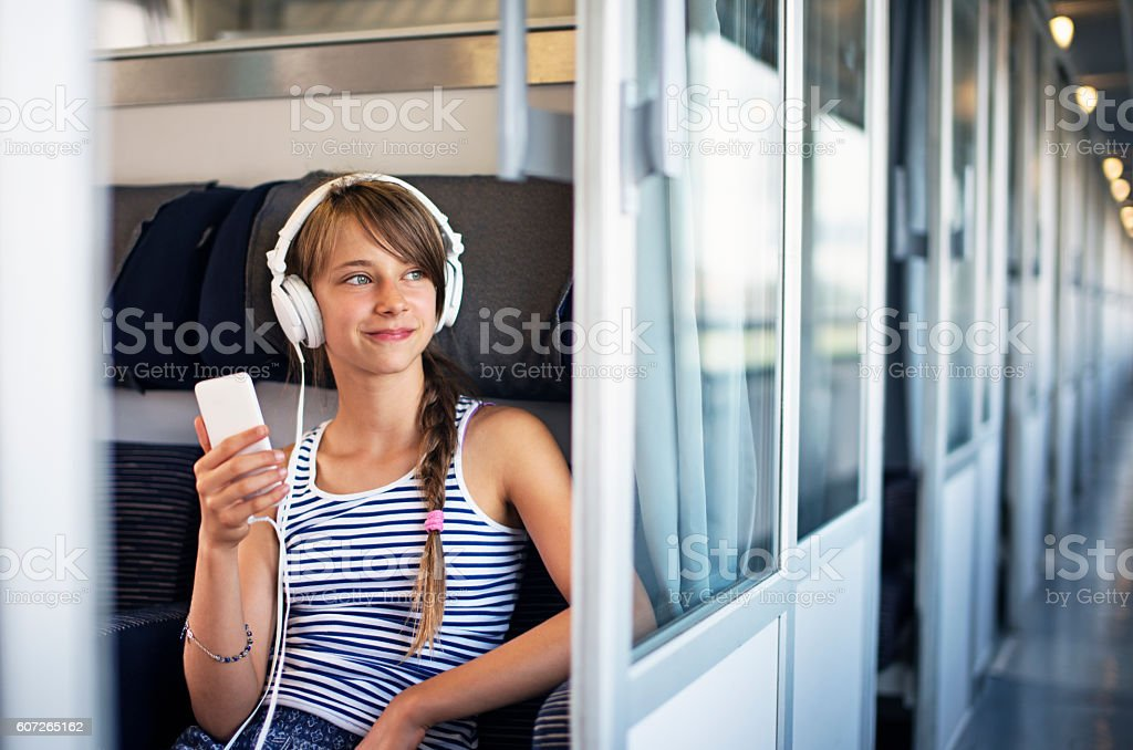 Teenage girl travelling on train in Italy stock photo