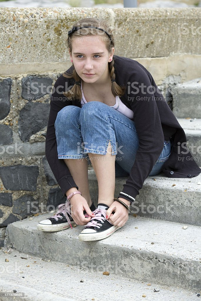 Teenage girl tying shoelaces royalty-free stock photo