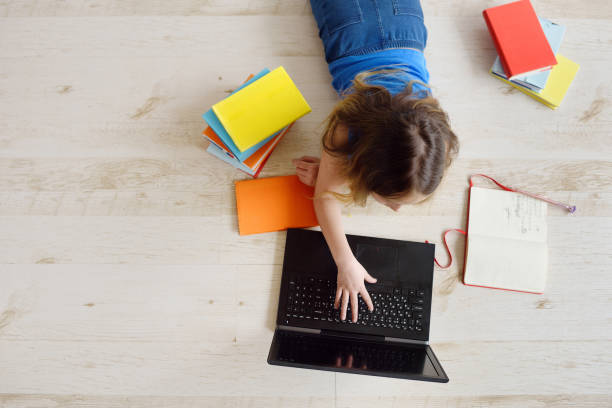 teenage girl uses a laptop. online education, home schooling. communication on the internet, chats. - didattica a distanza foto e immagini stock
