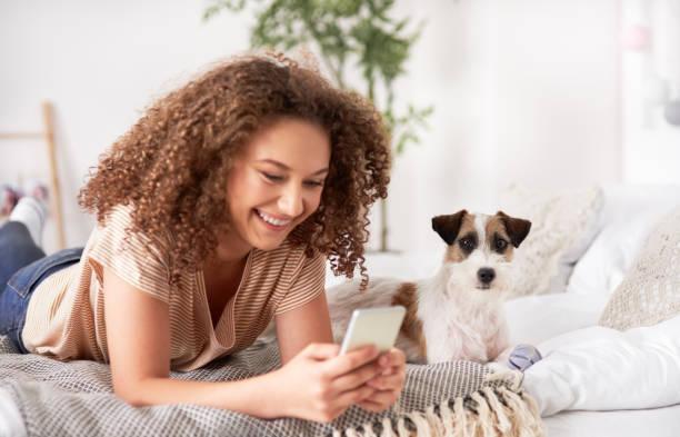 Teenager-Mädchen mit Handy und liegen datieren auf dem Bett – Foto