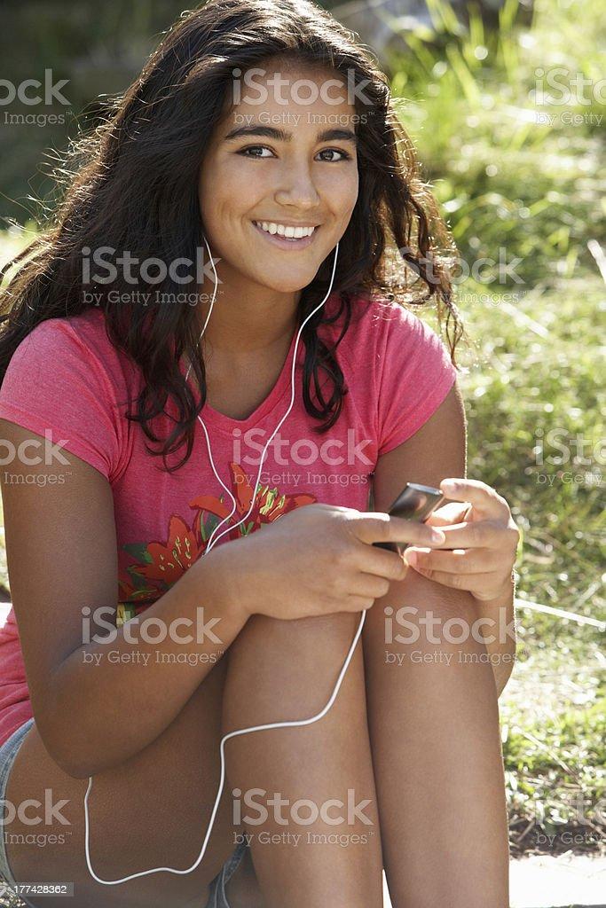 Teenage girl using mp3 player outdoors stock photo