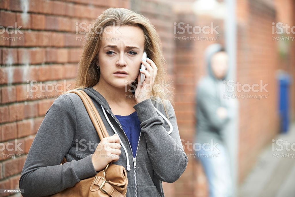 Teenage Girl Using Phone As She Feels Intimidated stock photo