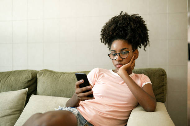 Teenage girl using smart phone on couch stock photo