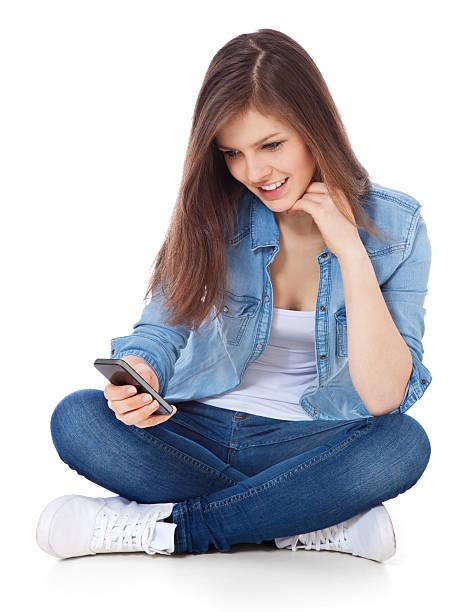 Teenage girl using smart phone stock photo