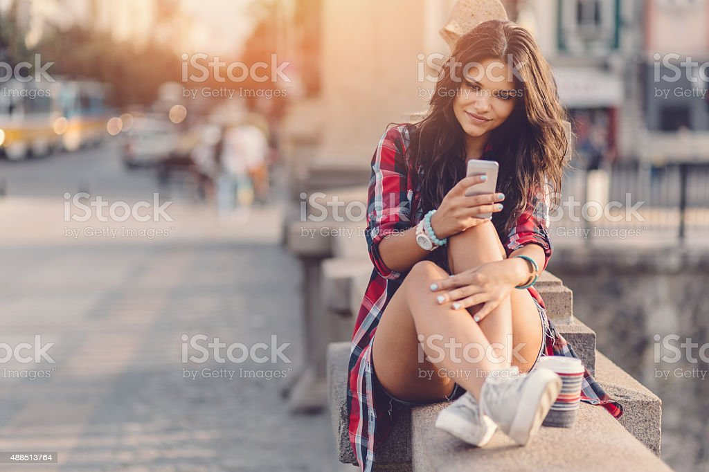 Teenage girl using smartphone in the city stock photo