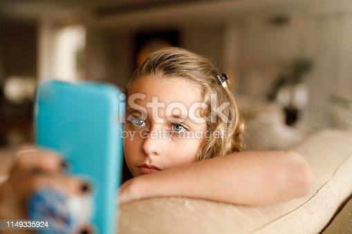 istock Teenage girl using social media on phone 1149335924