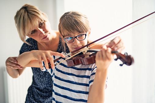istock Teenage girl violin lesson 611859684