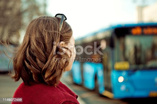 Young girl standing at a bus stop in the city