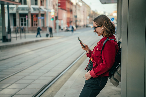 Teenage girl waiting for tramway, bus or taxi