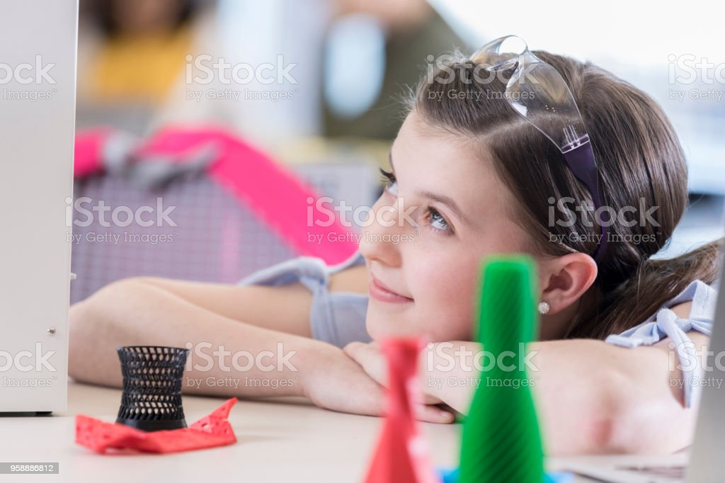 Teenage girl waits patiently as 3d printer produces her design stock photo