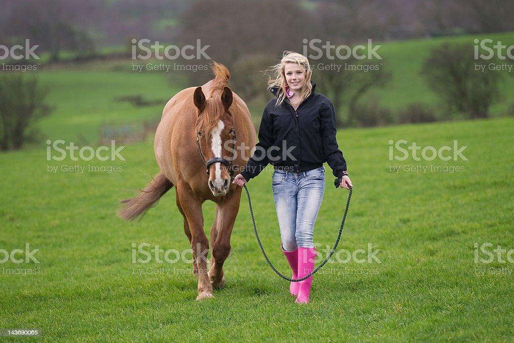 Teenage girl walking horse in field stock photo