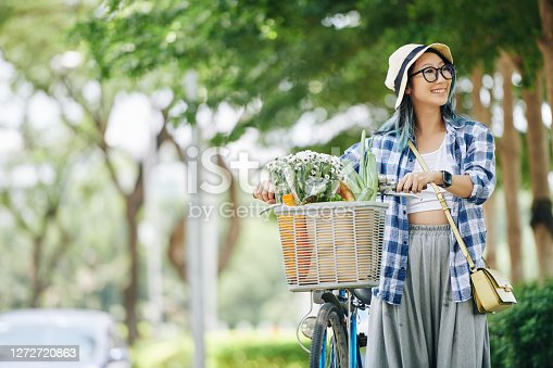Happy pretty Chinese teenage girl enjoying walking in park with her bicycle and looking around