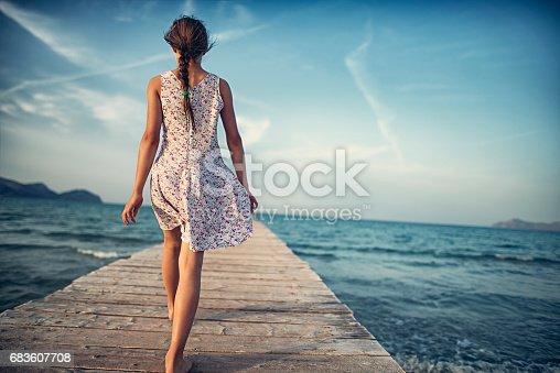 Teenage girl walking on sea pier. Beautiful sunny day of vacations. Playa de Muro, Majorca, Spain.
