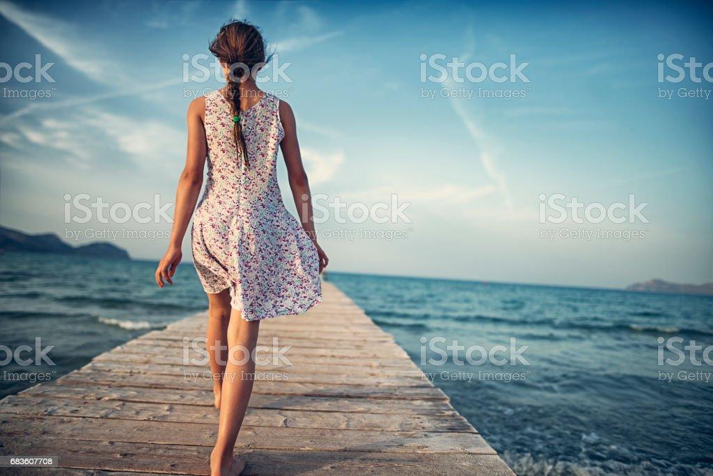 Teenage girl walking on sea pier stock photo