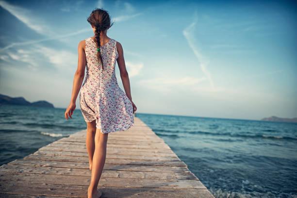adolescente, marche sur la jetée de la mer - fille dos photos et images de collection