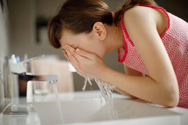 Teenage girl washing her face in the bathroom stock photo