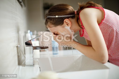 Teenage girl washing her face with water