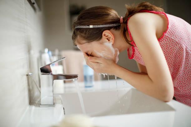 Teenager-Mädchen waschen ihr Gesicht mit Wasser – Foto