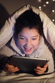 Teenage Girl Watching Movie On Laptop In Bedroom