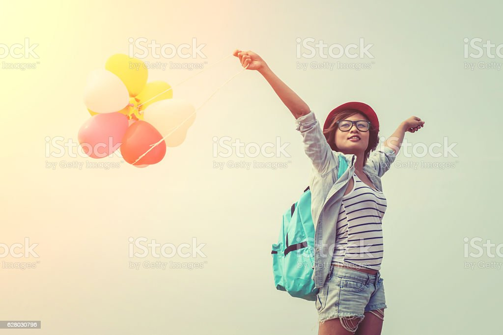 Teenage girl wearing glasses, holding balloons colored - foto de stock
