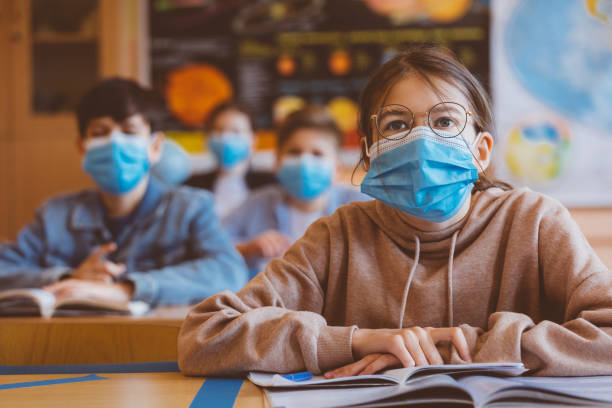 Teenage girl wearing N95 face mask at school stock photo