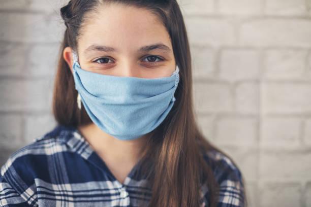 Teenager-Mädchen trägt schützende Gesichtsmaske für Sicherheit und Schutz während Coronavirus COVID-19 – Foto