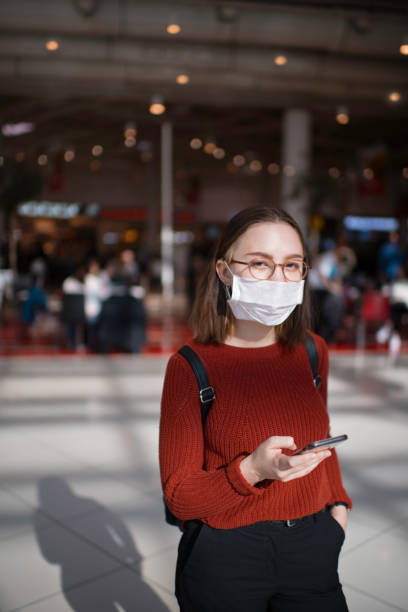 Teenage girl wearing protective face mask in a public place