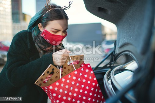 Young woman with Christmas gifts in car