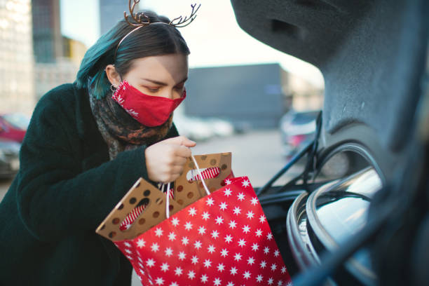 Teenage girl wearing protective face mask in car after Christmas shopping during COVID-19 pandemic
