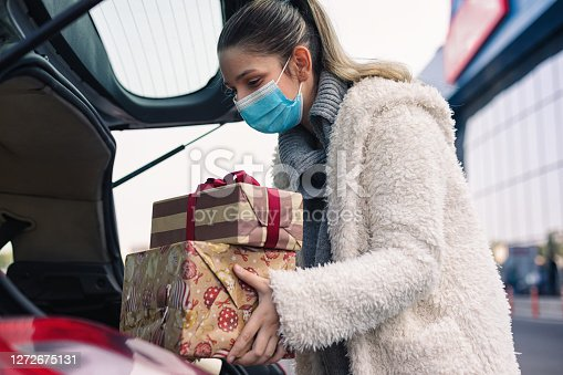 Teenage girl packing Christmas gifts in a car after shopping. She wears a protective mask to protect from corona virus COVID-19.