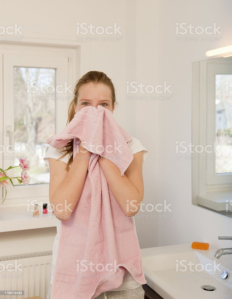 Teenage girl wiping her face with towel stock photo