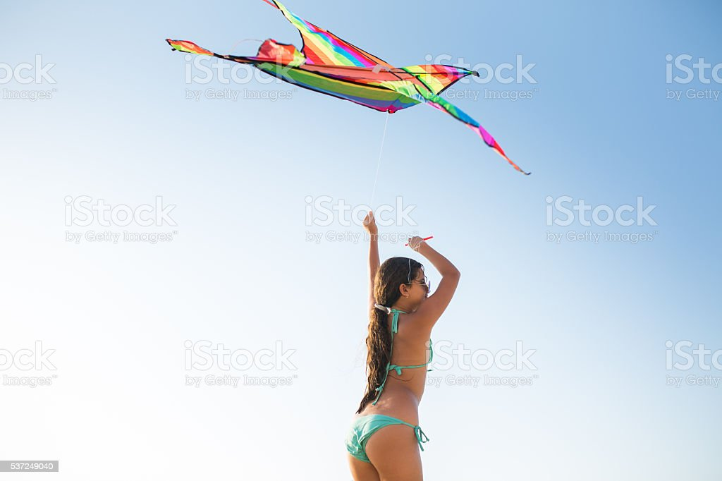 Teenage girl with a kite against the clear sky. stock photo
