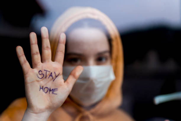Teenage girl with a surgical maks standing and looking through the window and showing 'stay home' message written on her hand Caucasian teenage girl with yellow hoodie and a surgical mask standing and looking through the window and showing 'stay home' message written on her hand. stay at home order stock pictures, royalty-free photos & images