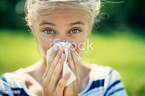 Portrait of teenage girl blowing her nose on a summer day. The girl is allergic to the pollen. Nikon D850