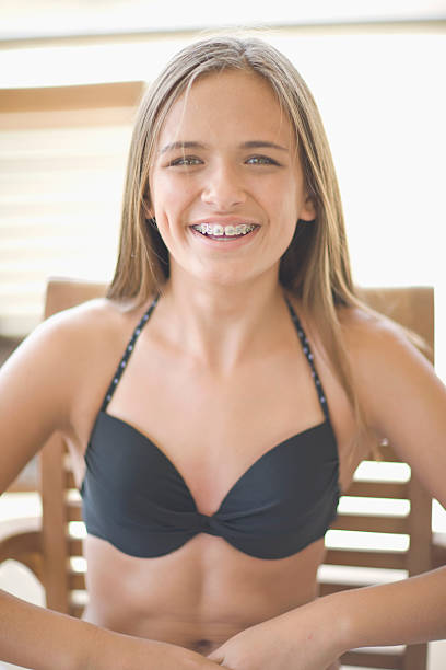 Teenage girl with braces wearing bikini  12 13 years stock pictures, royalty-free photos & images