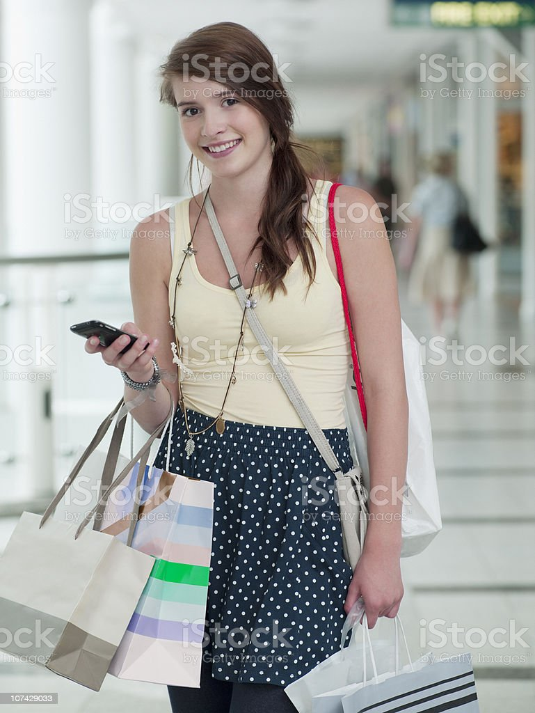 Teenage girl with cell phone carrying shopping bags in mall royalty-free stock photo