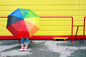 Teenage girl with colorful umbrella sitting in front of yellow background, wearing red sneakers.