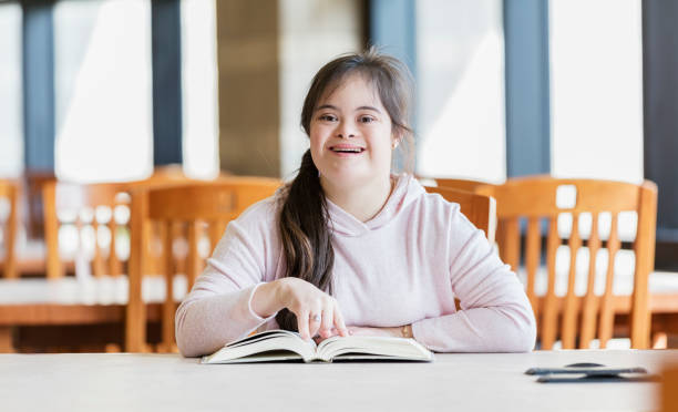Teenage girl with down syndrome reading in library A 17 year old mixed race Hispanic and Caucasian teenage girl with down syndrome, sitting at a table in the library, reading a book. She is a high school student, studying. She is smiling confidently at the camera. learning difficulty stock pictures, royalty-free photos & images