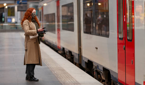 Teenage girl with facial mask at the railway station waiting for the train doors to open stock photo