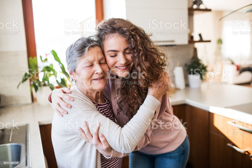 A teenage girl with grandmother at home, hugging. stock photo