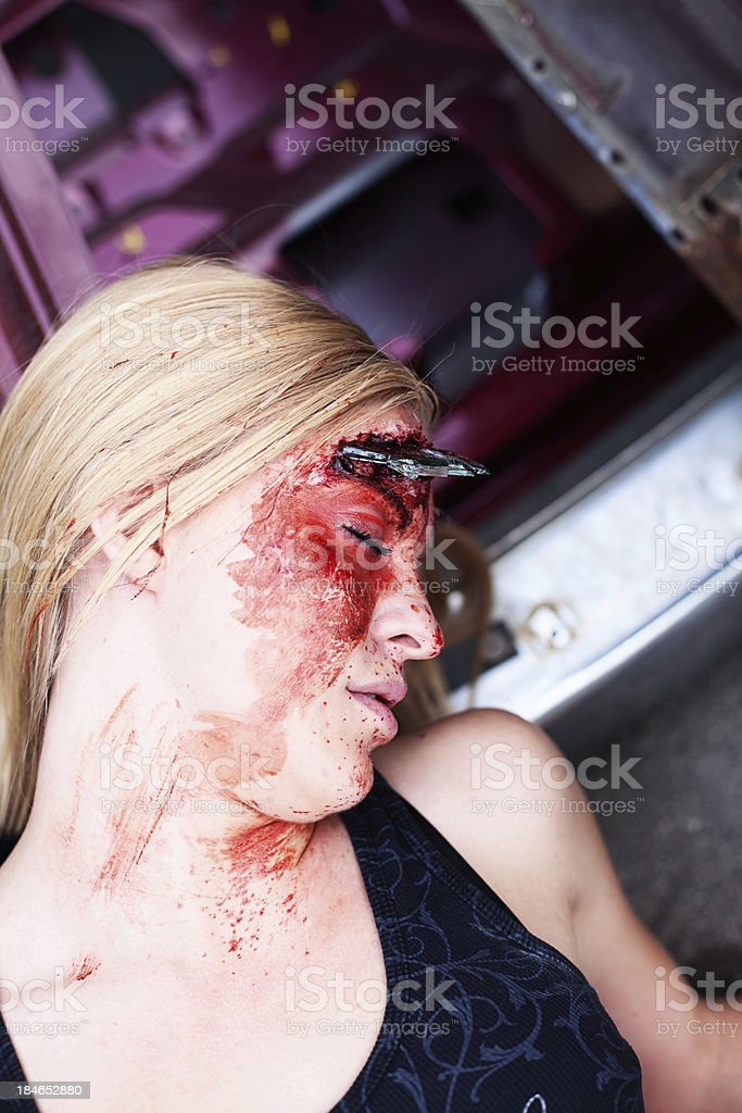 Young woman with laying on the ground with blood on her face after an...