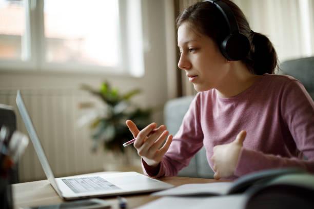 teenager-mädchen mit kopfhörern mit online-schulklasse zu hause - jugendalter stock-fotos und bilder