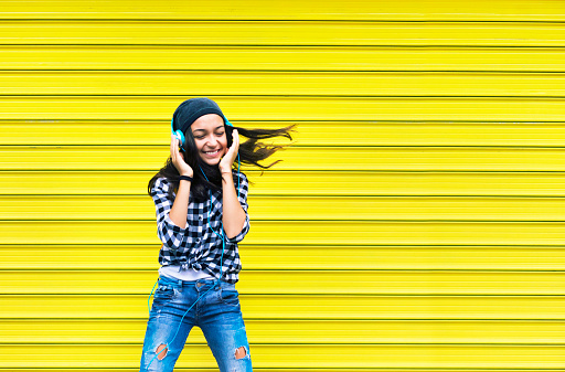 Beautiful teenage girl with headphones dancing to the music.