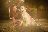 Teenage girl with her dog in the park - shot at sunset with lens flares on purpose - 5DII + 135mm/f2 + reflector