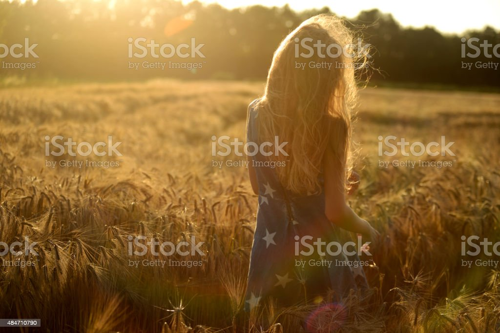 Teenage girl with long blond hair walking in barley field stock photo