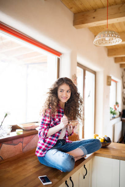 Teenage girl with long curly hair at home eating granola smart phone picture id698600940?b=1&k=6&m=698600940&s=612x612&w=0&h=7gfbysvkxgya p0yejaqf08jhfea vaqa0 gyikohmw=